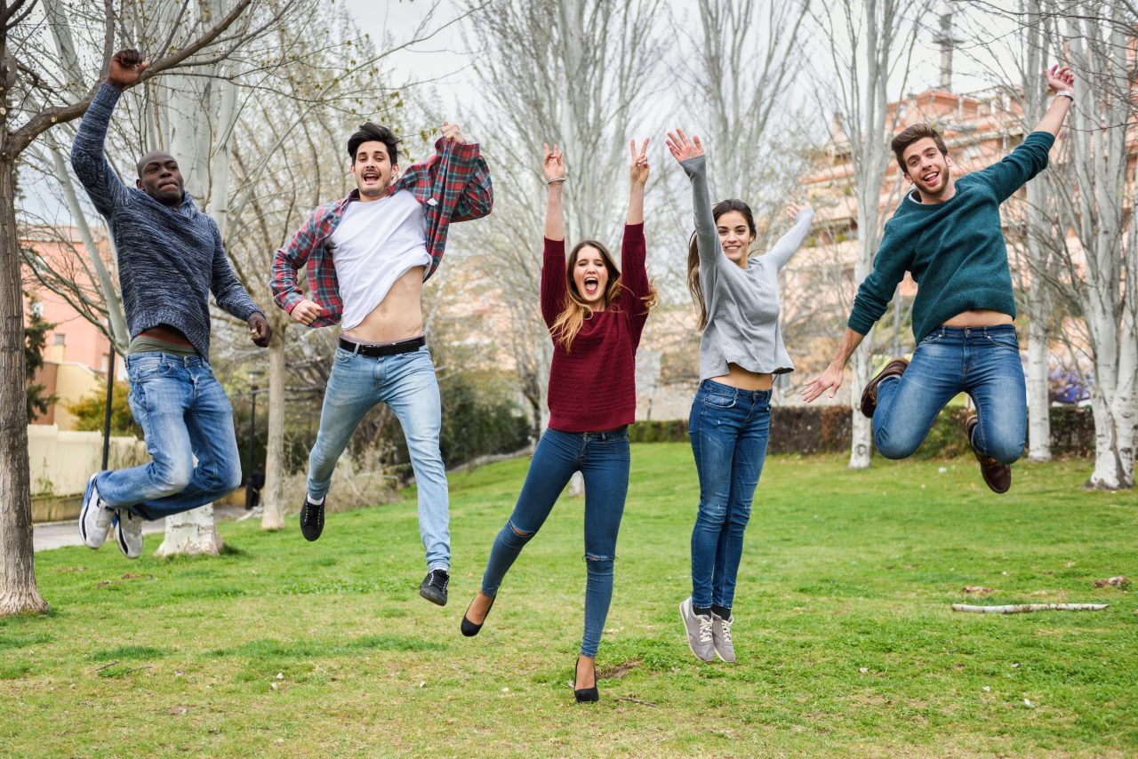 Group of multi-ethnic young people jumping together outdoors